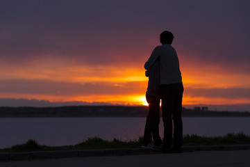Sillhouette of couple holding together at sunset