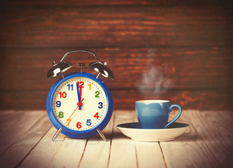 Cup of coffee and alarm clock