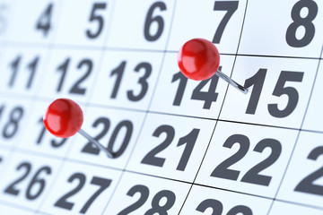 Closeup of the calendar with red pins. Soft focus