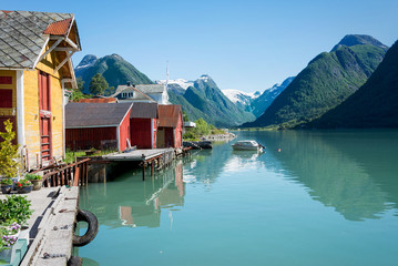 Fjord, mountains, boathouse and reflection in Norway
