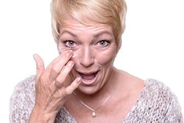Ältere Frau trägt Anti-Aging Creme auf