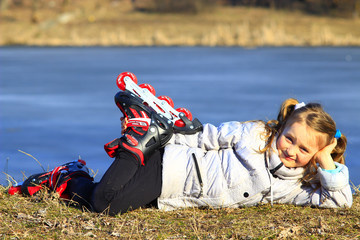 young girl in roller skates lays on the ground