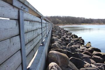 Holzbeschlag und Steine am Wasser