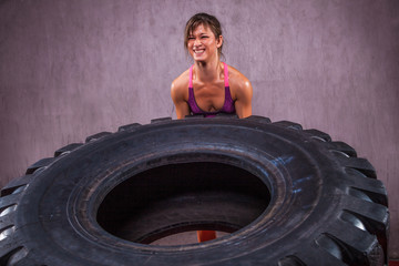 Fit young Woman Doing  Exercise With Tire