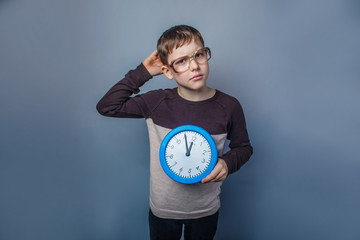 European-looking boy of ten years holding a wall clock reflected