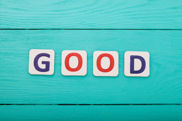 Word good on blue wooden background