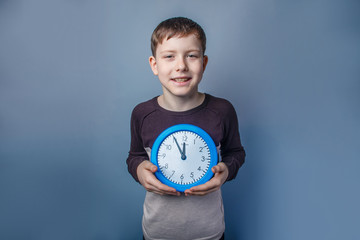 European-looking boy of ten years holding a wall clock on a gray