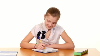 Cute school girl sitting, thinking and writing homework, essay