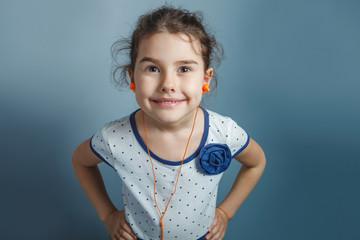 Teen girl of European appearance five years in headphones listen