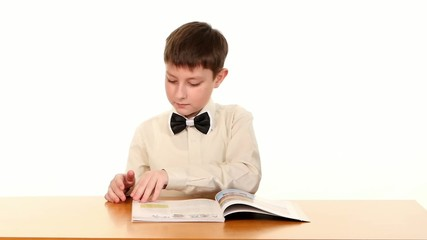 Little school boy looking for some information in the book, on