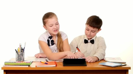 School children sitting by the table and doing homework, on