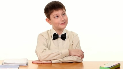 Little boy sitting at the table and sighing, on white background