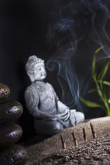 stone sitting buddha and frankincense