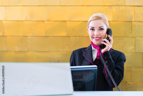 Hotel Rezeptionistin telefoniert mit Gast  - 81199839
