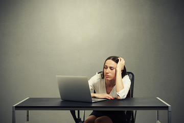 tired businesswoman looking at monitor
