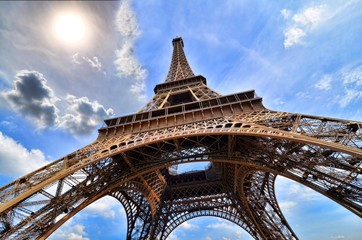 Eiffel Tower, Paris, France upward view with sun and blue sky