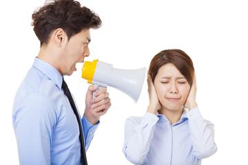 Businessman using megaphone to scream at businesswoman