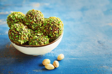 Tasty homemade pistachio candies on wooden table