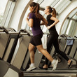 gym shot - two young women running on machines, treadmill
