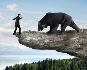 Businessman against black bear balancing on cliff with sky trees