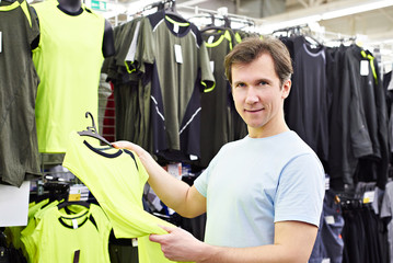 Happy man shopping for sport t-shirt in shop