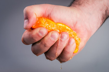 Male hand squeezing orange.