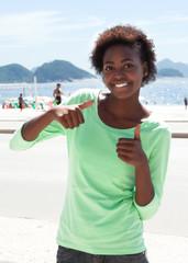 Brasilianerin an der Copacabana zeigt beide Daumen