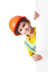 Portrait of little boy in hardhat with billboard