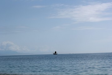 single black boat ship sailing on calm blue sea with clear blue