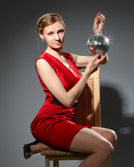 Young woman holding disco ball sitting on grey background