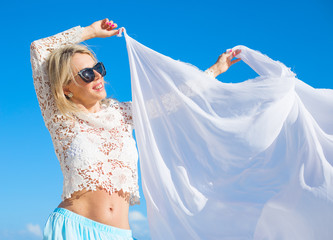 Carefree woman holding white fabric in wind