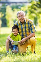 Grandfather and grandson using digital tablet in park