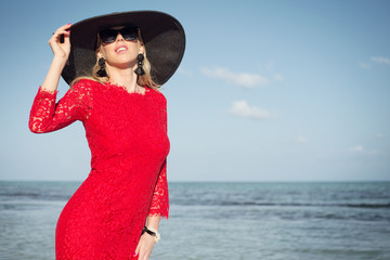 Woman with black summer hat and red dress on the beach