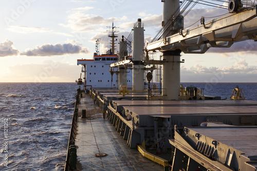 Cargo ship underway at sunset - 81211252