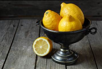 Lemons in a metal vase on a gray  table