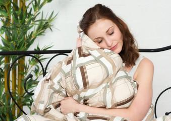 Junge Frau kuschelt sich an der Bettdecke an