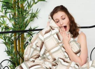 Junge Frau kuschelt mit der Bettdecke und gähnt
