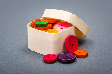 Small wooden box with colorful buttons