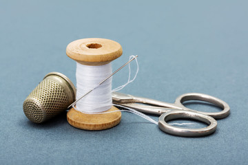 Sewing thread, needle, thimble and scissors