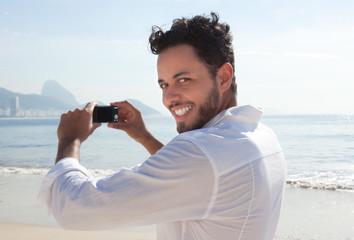 Brasilianer macht Urlaubsfoto an der Copacabana