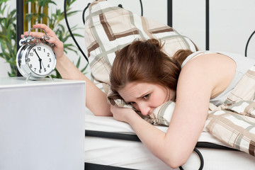Frau ist genervt vom klingelnden Wecker