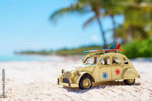 Small toy car on the beach with surfboards on the roof - 81213895