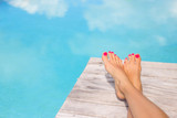 Bare woman feet on wooden deck by the swimming pool - 81214013