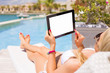 Woman using ipad while relaxing by the swimming pool