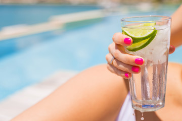 Woman holding refreshing cold drink while sunbathing by the pool