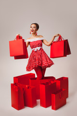 Happy Woman Holding Up Shopping Bags. Pin-up retro style.
