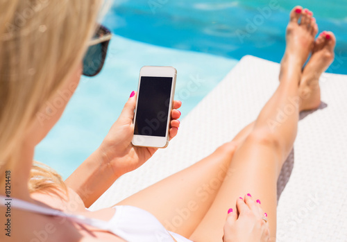 Leinwanddruck Bild Woman sunbathing in chair by the pool and using mobile phone