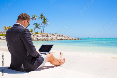 Businessman using laptop computer on the beach
