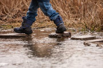 Kleinkind geht über Steine im Wasser
