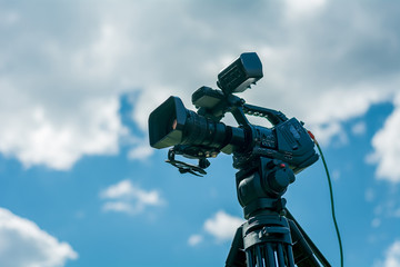 Professional video camera on a tripod against the blue sky
